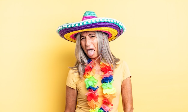 Hübsche frau mittleren alters mit fröhlicher und rebellischer haltung, scherzen und herausstreckender zunge. mexikanisches partykonzept