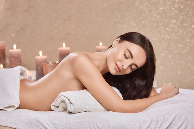 Hübsche frau nach körpertherapie und massage im spa mit angenehmem gesicht und kerzen