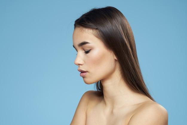 Hübsche frau nackte schultern haarpflege nahaufnahme bank blaue wand.