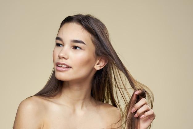 Hübsche frau nackte schultern kosmetik saubere haut haarpflege beige.