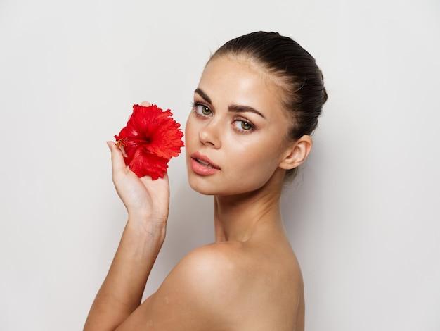 Hübsche frau nackte schultern rote blume beschnittene ansicht studio