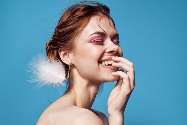 Hübsche frau nackte schultern und flauschige ohrringe heller make-up-blauer hintergrund