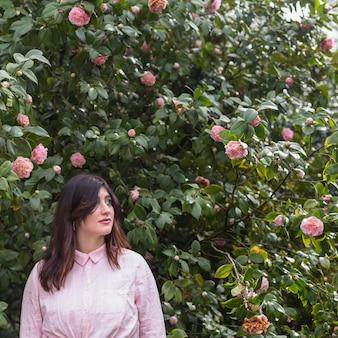 Hübsche frau nahe den rosa blumen, die auf grünen zweigen wachsen