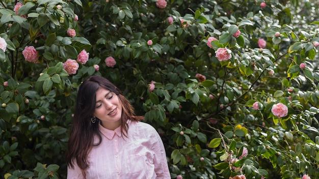 Hübsche frau nahe vielen rosa blumen, die auf grünen zweigen wachsen