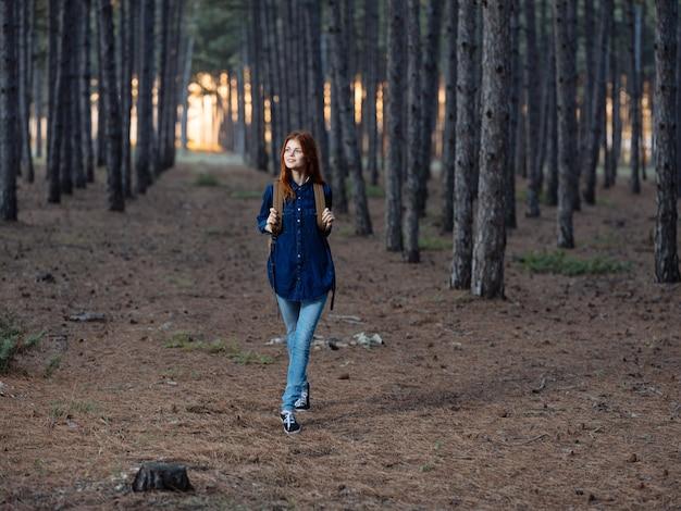 Hübsche frau reist im wald mit einem rucksack auf dem rücken und in einem blauen hemd