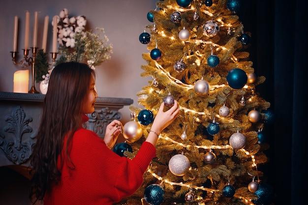 Hübsche frau schmückt weihnachtsbaum helle kugeln lichter und girlanden auf kiefernkamin im hintergrund neujahrsatmosphäre romantische festliche stimmung frau in gemütlichem strickpullover