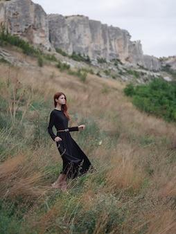 Hübsche frau schwarzes kleid zu fuß bergreisen
