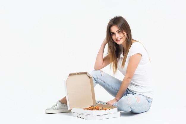Hübsche frau sitzt auf dem boden mit einem pizzakarton und nimmt ein stück.