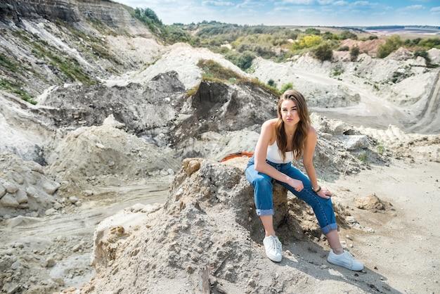 Hübsche frau sitzt im sand im steinbruch. zeit in den sommerferien genießen