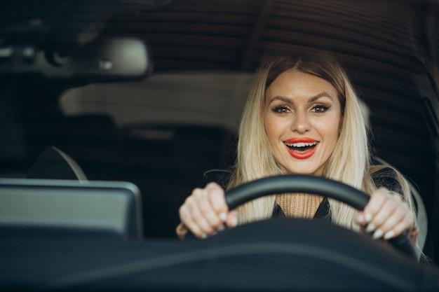 Hübsche frau sitzt in ihrem auto
