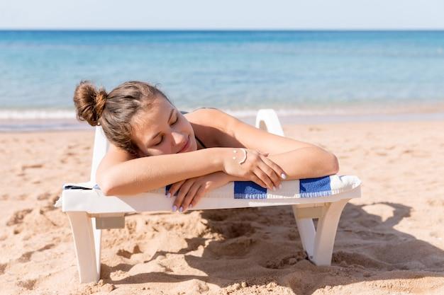Hübsche frau sonnt sich auf der sonnenliege am strand und hat ein lächelndes gesicht aus sonnencreme auf der hand.