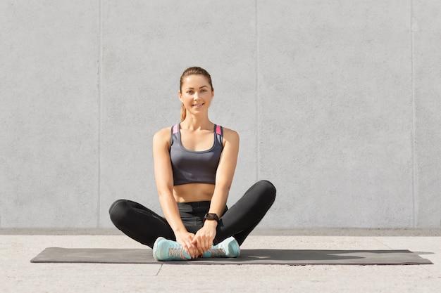 Hübsche frau treibt regelmäßig sport, trägt sportbekleidung, sitzt mit gekreuzten beinen auf der matte im fitnessstudio und ruht sich nach yoga-übungen aus