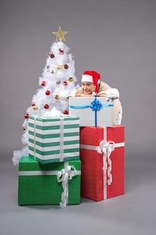 Hübsche frau um geschenke auf grau