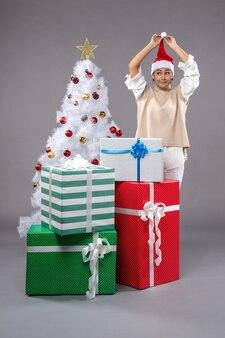 Hübsche frau um weihnachtsgeschenke auf grau