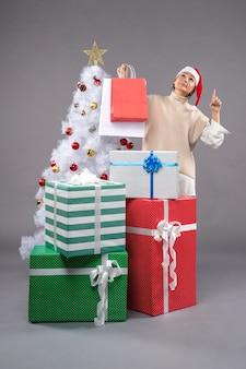 Hübsche frau um weihnachtsgeschenke auf licht