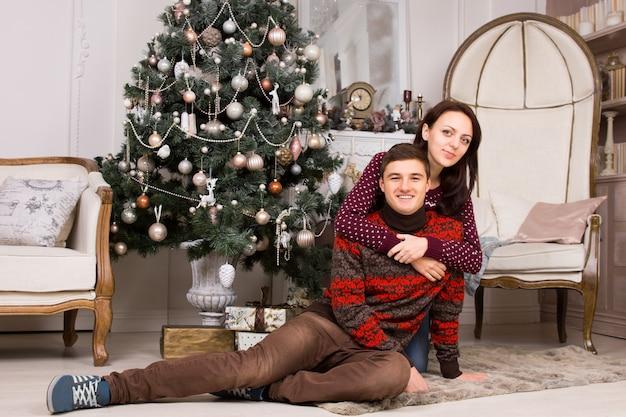 Hübsche frau umarmt lächelnden jungen mann beim ausruhen auf dem boden teppich in der nähe des schönen weihnachtsbaums und des großen eleganten stuhls.