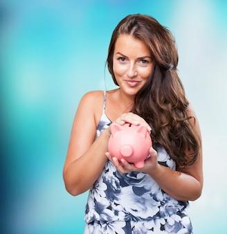 Hübsche frau von ihrem sparschwein kümmert