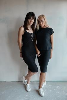 Hübsche frau zwei in einem schwarzen kleid innen