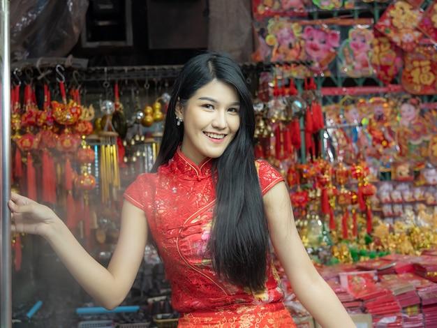 Hübsche frauen des porträtbildes tragen rotes cheongsam-kleid.