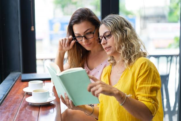 Hübsche frauen, die lehrbuch lesen und kaffee im café trinken