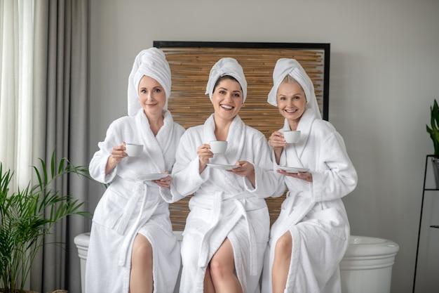 Hübsche frauen in bademänteln, die sich ausruhen