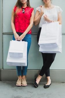 Hübsche frauen mit weißen einkaufstaschen
