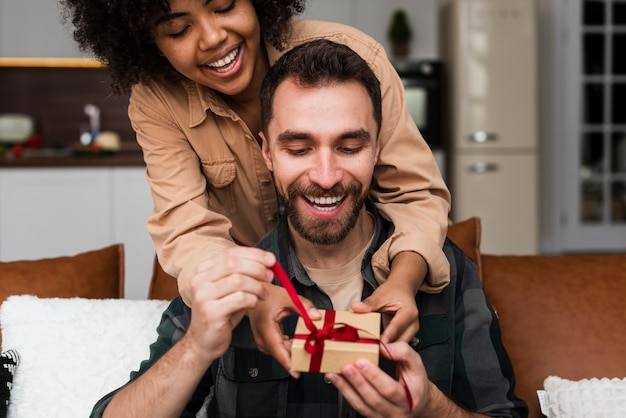 Hübsche frauenfrau, die ihrem freund ein geschenk anbietet