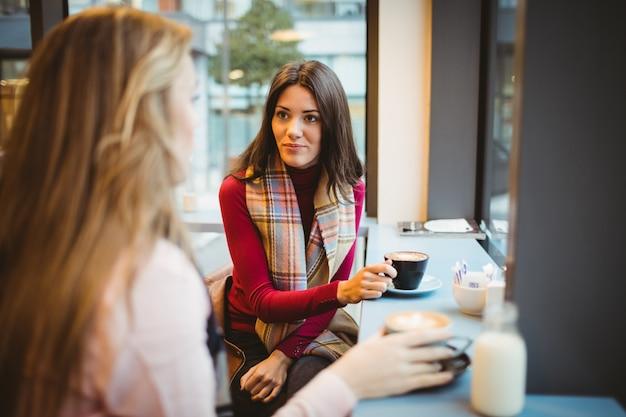 Hübsche freunde, die beim kaffee plaudern