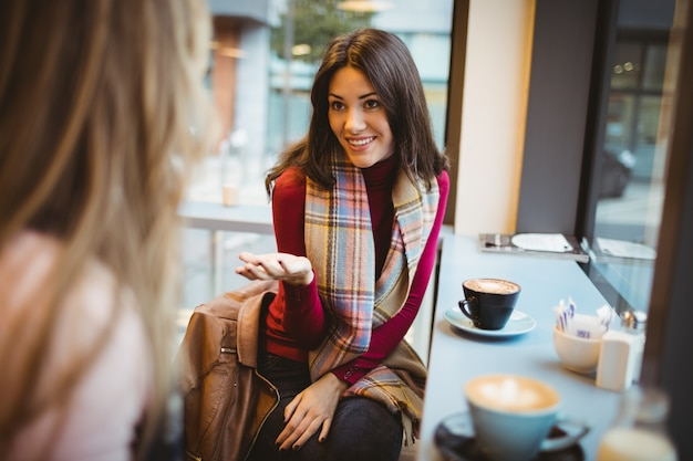Hübsche freunde, die über kaffee im café plaudern
