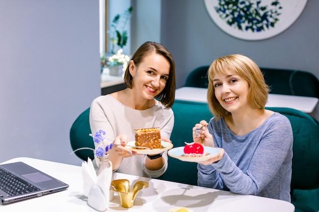 Hübsche freundinnen, die geschmackvolle bunte kuchen am innencafé, lächelnd glücklich teilen. frauenfreundschaft