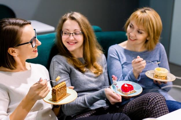 Hübsche freundinnen, die geschmackvolle nachtischkuchen am innencafé, lächelnd glücklich essen. treffen der besten freunde