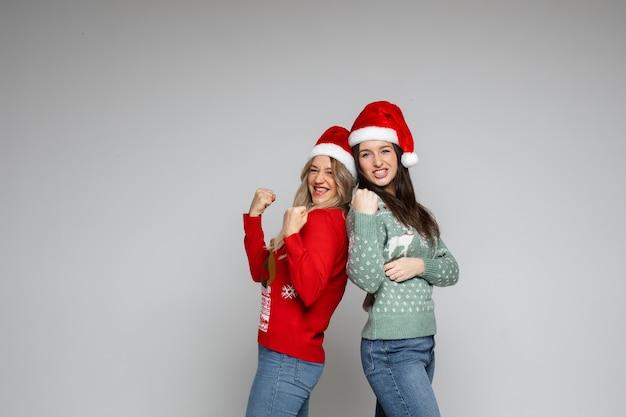 Hübsche freundinnen in rot-weißen weihnachtsmützen haben viel spaß