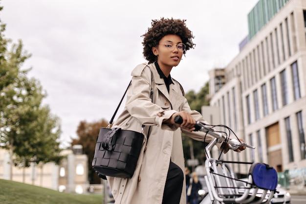 Hübsche fröhliche dame geht mit fahrrad
