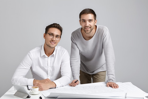 Hübsche, fröhliche junge männliche unternehmer oder designarbeiter sitzen am arbeitsplatz, umgeben von blaupausen