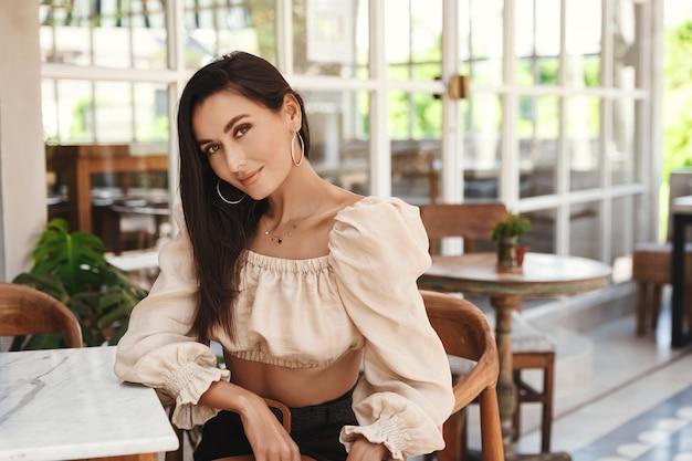 Hübsche gebräunte frau, die im hotelrestaurant sitzt und lächelt