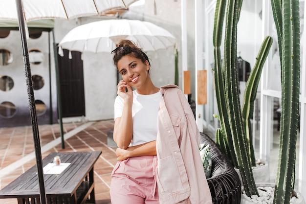 Hübsche gebräunte frau im rosa und weißen outfit lehnt sich auf stuhl unter regenschirm im straßencafé