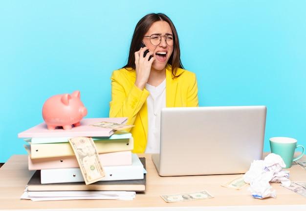 Hübsche geschäftsfrau, die auf ihrem schreibtisch sitzt und mit einem laptop arbeitet