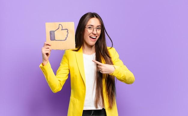 Hübsche geschäftsfrau, die ein symbol der sozialen medien hält