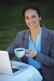 Hübsche geschäftsfrau, die kaffee trinkt und laptop verwendet