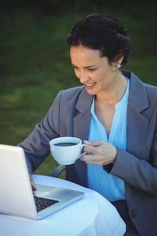 Hübsche geschäftsfrau, die laptop verwendet und kaffee trinkt