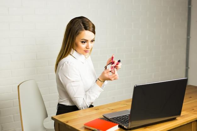 Hübsche geschäftsfrau, die make-up im büro macht