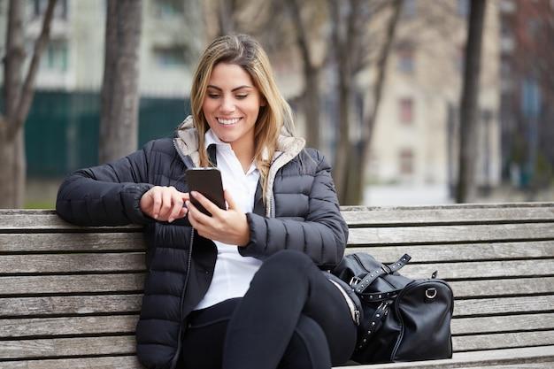 Hübsche geschäftsfrau, die mit mobile in der städtischen umwelt sitzt auf einer bank spricht