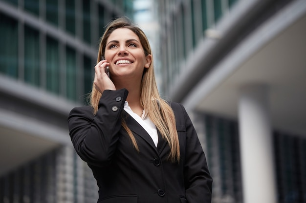 Hübsche geschäftsfrau, die mit mobile in der städtischen umwelt spricht