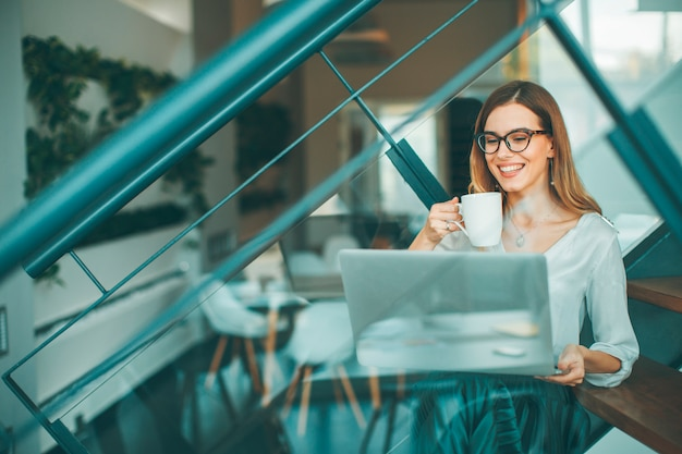 Hübsche geschäftsfrau, die oh die bürotreppe sitzt, kaffeepause hat und netz-surfendes internet