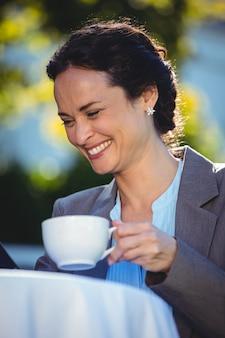Hübsche geschäftsfrau, die tablette verwendet und einen kaffee trinkt