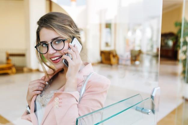 Hübsche geschäftsfrau, junge dame, die lächelt und per telefon spricht, schaut und in der halle steht. tragen sie stilvolle rosa jacke, brille. bild durch glastür.