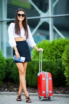 Hübsche geschäftsfrau mit rotem koffer nahe flughafen