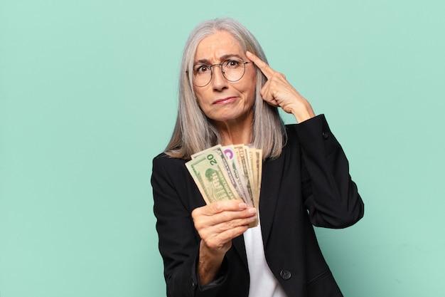 Hübsche geschäftsfrau yseniors mit dollarbanknoten. geldkonzept