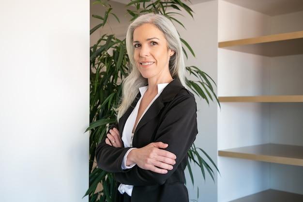 Hübsche grauhaarige geschäftsfrau, die mit gefalteten händen steht. porträt des zuversichtlichen jungen hübschen weiblichen büroarbeitgebers im anzug, der bei der arbeit aufwirft und lächelt. geschäfts-, unternehmens- und managementkonzept Kostenlose Fotos