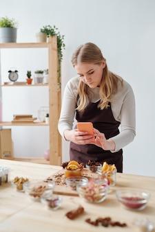 Hübsche handwerkerin mit smartphone, die foto von zutaten und anderen aromatischen sachen für die herstellung von handgemachter seife auf tisch im studio macht